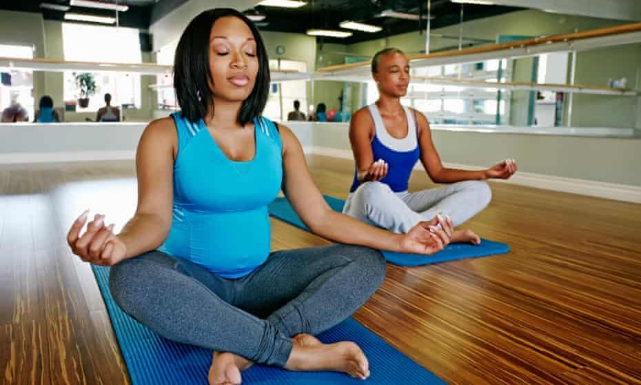 African American women meditating in yoga studio