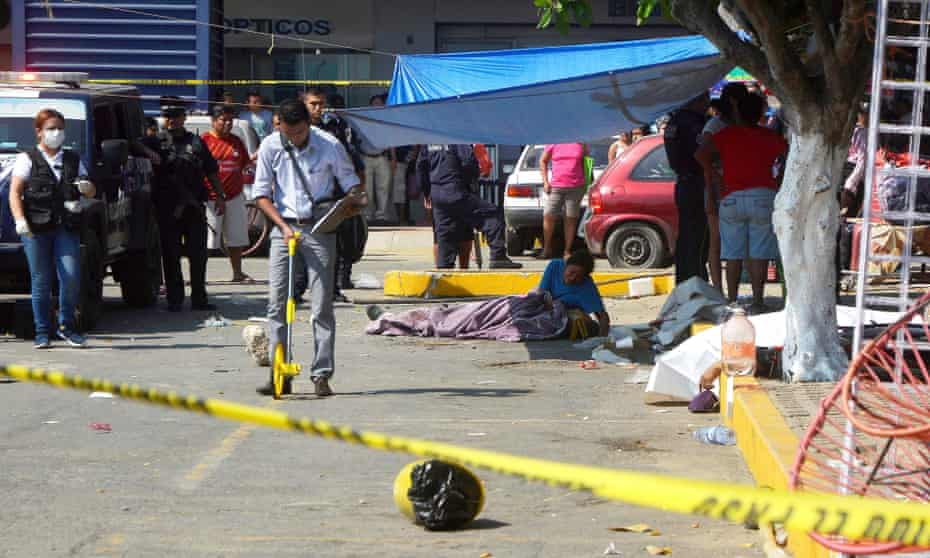 A woman cries over the corpse of her murdered family member while forensic personnel work at the scene of the crime in the parking lot of a shopping center in Acapulco, Guerrero, Mexico, on 4 January 2017.