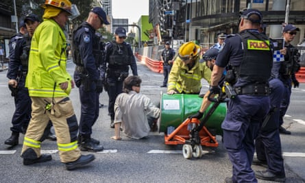 An activist from Extinction Rebellion with his arm in a barrel of cement protests in Brisbane on Tuesday