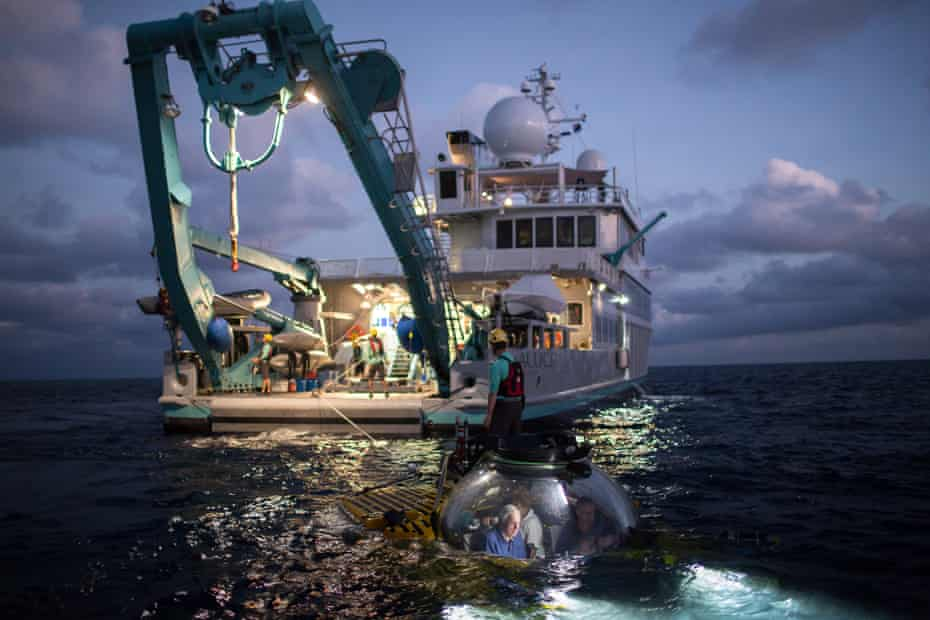 The Triton Submersible, and Sir David Attenborough within it, is lowered into the Great Barrier Reef