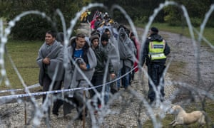 A queue of refugees crossing the Hungarian-Croatian border, seen through barbed wire