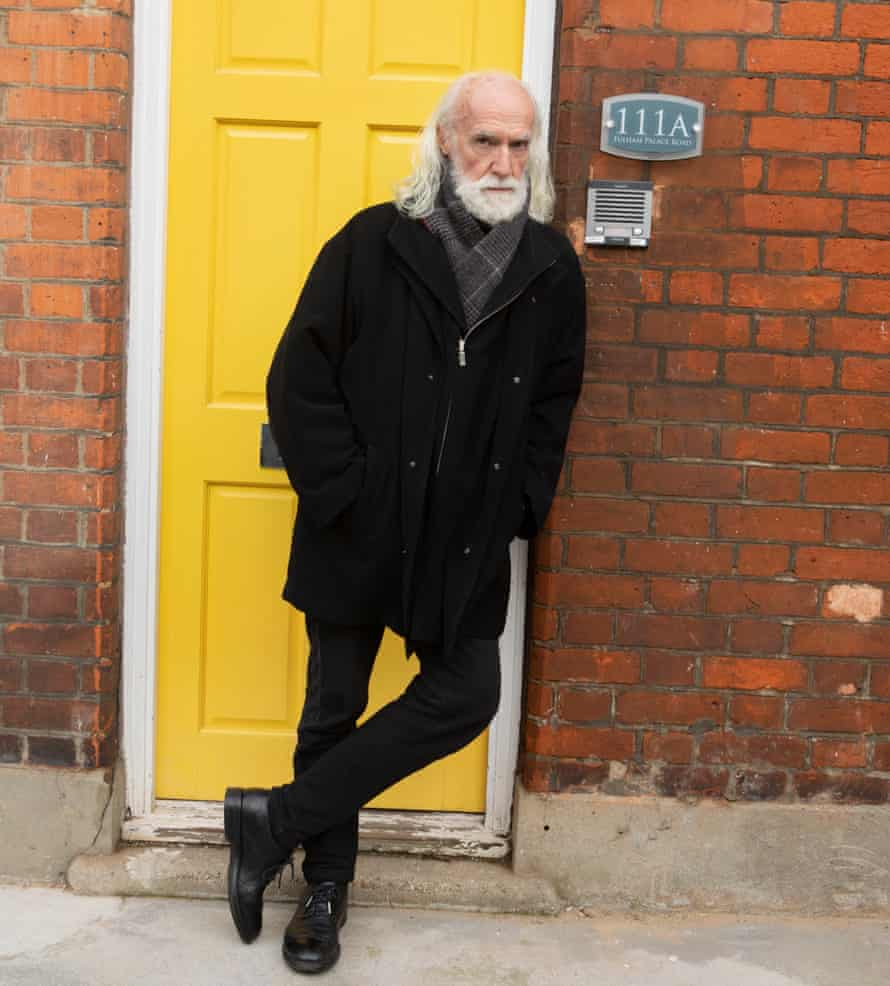 David Gant standing in front of a yellow door wearing a black jacket and jeans