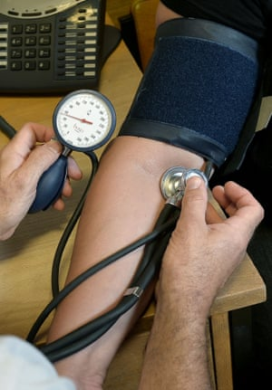 a doctor takes someones blood pressure with a sleeve around their arm and a stethoscope
