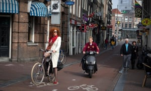 A cyclist and a moped rider share a bike lane.