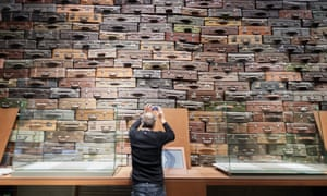 A visitor at the opening of the main exhibition of the Museum of the Second World War in Gdańsk, Poland. He is taking a picture in front of a display of piled up suitcases representing deportation.