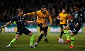 Newport's Robbie Wilmott surges forward as Manchester City's Oleksandr Zinchenko and Leroy Sane try to thwart him.