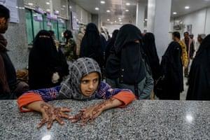 Girl waits at UNHCR cash distribution bank in Marib city