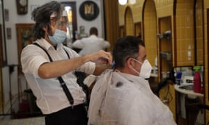 A barber cuts hair of a customer after small shops and businesses were allowed to reopen on Monday in Madrid