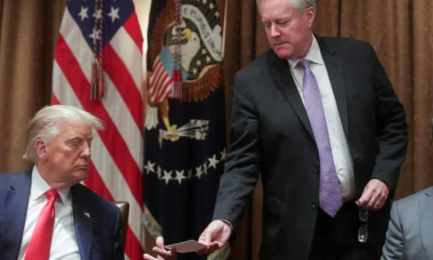 The then White House chief of staff, Mark Meadows, passes a note to Donald Trump in the cabinet room of the White House on 3 August 2020.