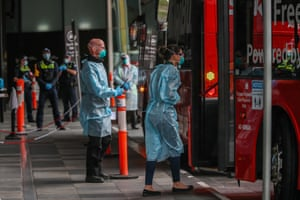 Hotel quarentine workers are seen in full PPE gear as they ask recently arrived international travellers to get off the bus and enter hotel quarantine in Melbourne.