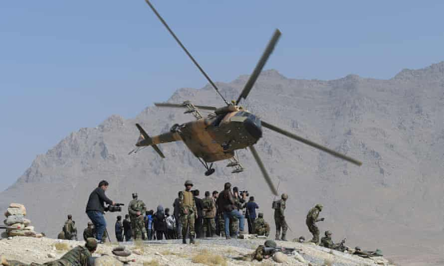 An Afghan air force Mi-17 helicopter flies past commandos during a military exercise on the outskirts of Kabul in October 2017