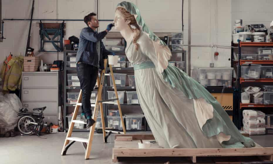 A man up a ladder working on the face of a giant figure of a woman leaning forward, standing on a plinth