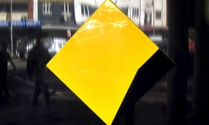 Pedestrians are reflected in a Commonwealth Bank logo sign outside a branch in Sydney