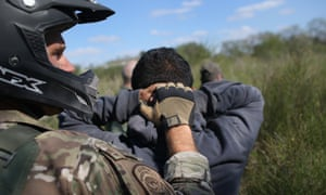 A US border patrol agent leads undocumented immigrants through the brush after capturing them near the Mexico border on 7 December 2015 near Rio Grande City, Texas.
