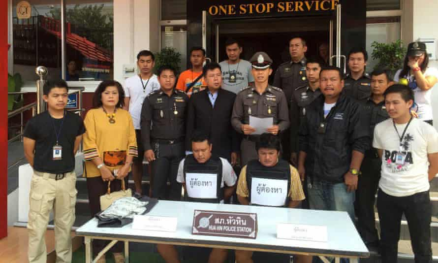 Hua Hin police stand behind two suspects arrested following the assault on the British couple and their son.