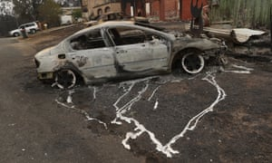 A burned out car outside a house in Conjola Park, New South Wales.