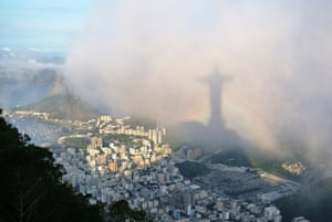 Rio de Janeiro as seen from Corcovado, with the shadow of Christ the Redeemer projected onto the clouds and framed by a rainbow.