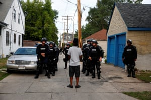 Police in riot gear assemble in an alley after disturbances following the shooting of a man in Milwaukee, Wisconsin