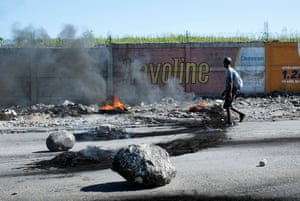 Rocks and burning tyres block a road running alongside the boundary wall of Port-au-Prince's main airport during anti-government protests in Haiti