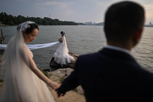 Couples pose for wedding photographers by the city's East Lake