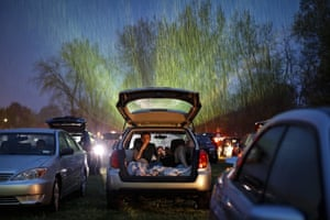 People watch the film Trolls World Tour in the rain at the Four Brothers drive-in theatre.