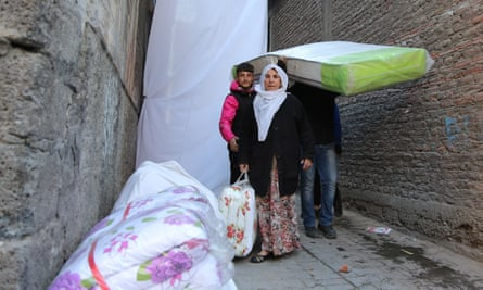 Kurdish residents flee with some of their belongings after new curfews were imposed in the Sur district of Diyarbakir