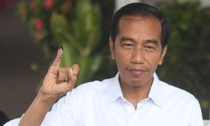 Joko Widodo shows his ink-stained finger after casting his vote in Jakarta