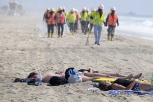 Huntingdon Beach, US. People sunbathe as workers clean the contaminated beach. The shoreline has been reopened after tests revealed non-detectable amounts of oil-associated toxins in ocean water