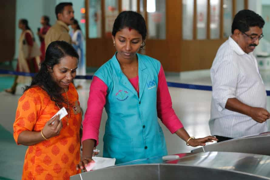 A metro worker helps a traveller with the automatic fare collection machine at Aluva metro station in Kochi