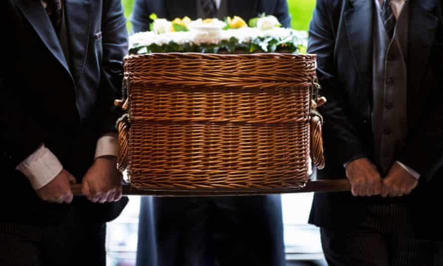 A wicker coffin carried by bearers.