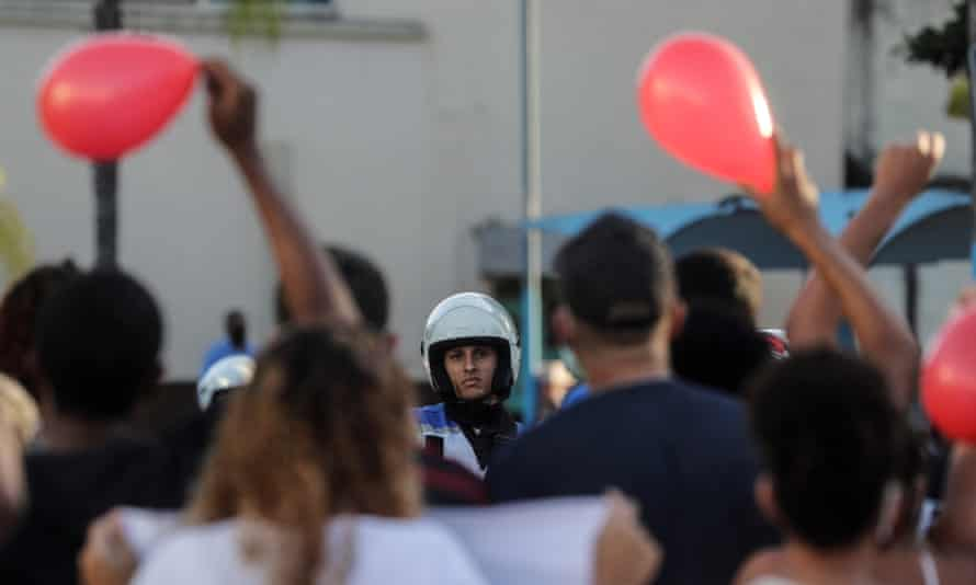 A policeman is seen in front of the protest carried out near the cemetery before the funeral of João Pedro on 14 May.