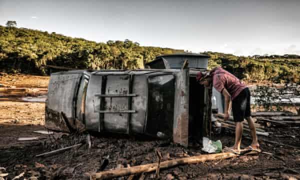 Onlooker looks inside a car left by mud.