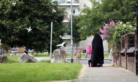 A Muslim woman and a child walk down a street.