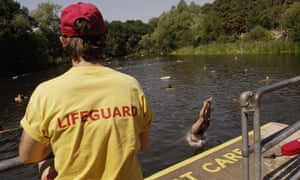 A lifeguard watches women swimming in the ladies' pond on Hampstead Heath.