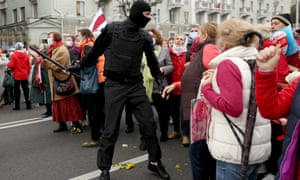 Masked Belarusian security officials confront confront older protesters during a rally to demand the resignation of Alexander Lukashenko.