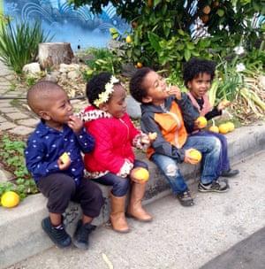 Local children enjoying the oranges grown in Ron Finley's garden.