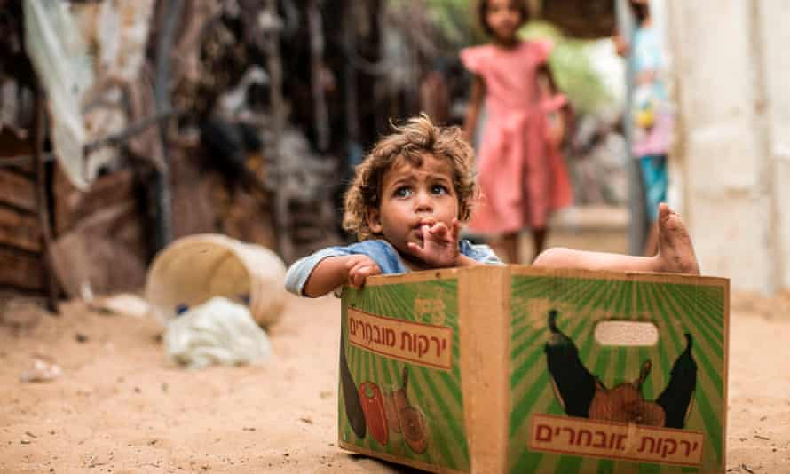 A Palestinian toddler sits inside a cardboard fruit box in Gaza City on August 8, 2017.