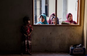 Lhoksukon, Aceh, Indonesia A Rohingya girl migrant stands as look out through the window at a shelter. Boats carrying over 500 of Myanmar's Rohingya refugees have arrived in Indonesia, many requiring medical attention