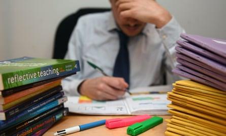 A school teacher next to piles of classroom books