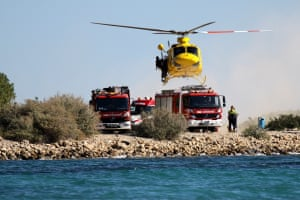 helicopter hovers above fire engines