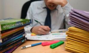 a teacher next to a pile of classroom books