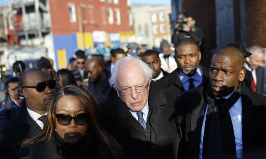 Democratic presidential candidate Bernie Sanders walks alongside the Rev Jamal Bryant, right, during a walking tour of the Sandtown-Winchester neighborhood of Baltimore.