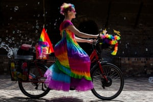 Norrie in a rainbow dress on a bicycle