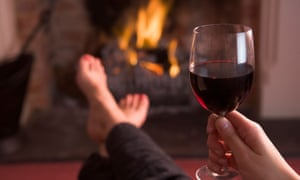 Drinking wine in front of a fire