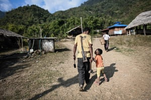 A man walking with his child ahead as the village prepares for the night's festivites