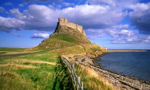 Lindisfarne Castle on Holy Island in Northumberland England UK with rocky beach in the foreground