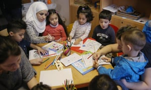 """Reading Initiative For Refugee Children LaunchBERLIN, GERMANY - DECEMBER 16: Immigrant mothers with their children look through games and books during the presentation of a new initiative to help children of refugees learn to read German at a shelter for migrants and refugees on December 16, 2015 in Berlin, Germany. The initiative, """"Reading Start for Refugee Children,"""" is being launched by the German Ministry of Education and Research. Germany is expected to receive over one million migrants seeking asylum in 2015 and is seeking a rapid integraiton of the newcomers into society and the job market, for which language instruction is a crucial component. (Photo by Sean Gallup/Getty Images)"""