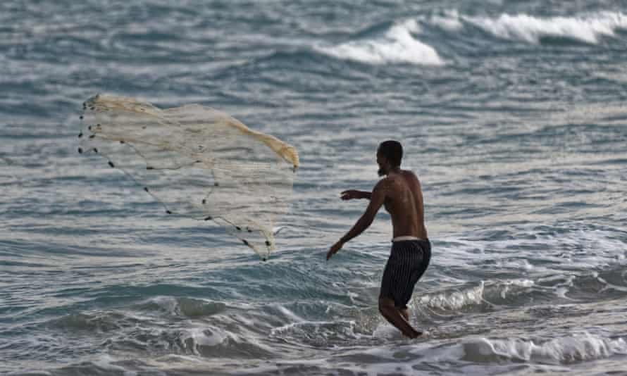 A Somali fisherman casts his nets at dusk on the beach