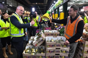 A stall holder hands his pineapple hat to Scott Morrison during a visit to Flemington markets in Sydney