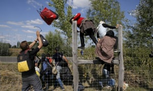 Migrants jump over a road protection fence as they leave a collection point in the village of Roszke, Hungary.